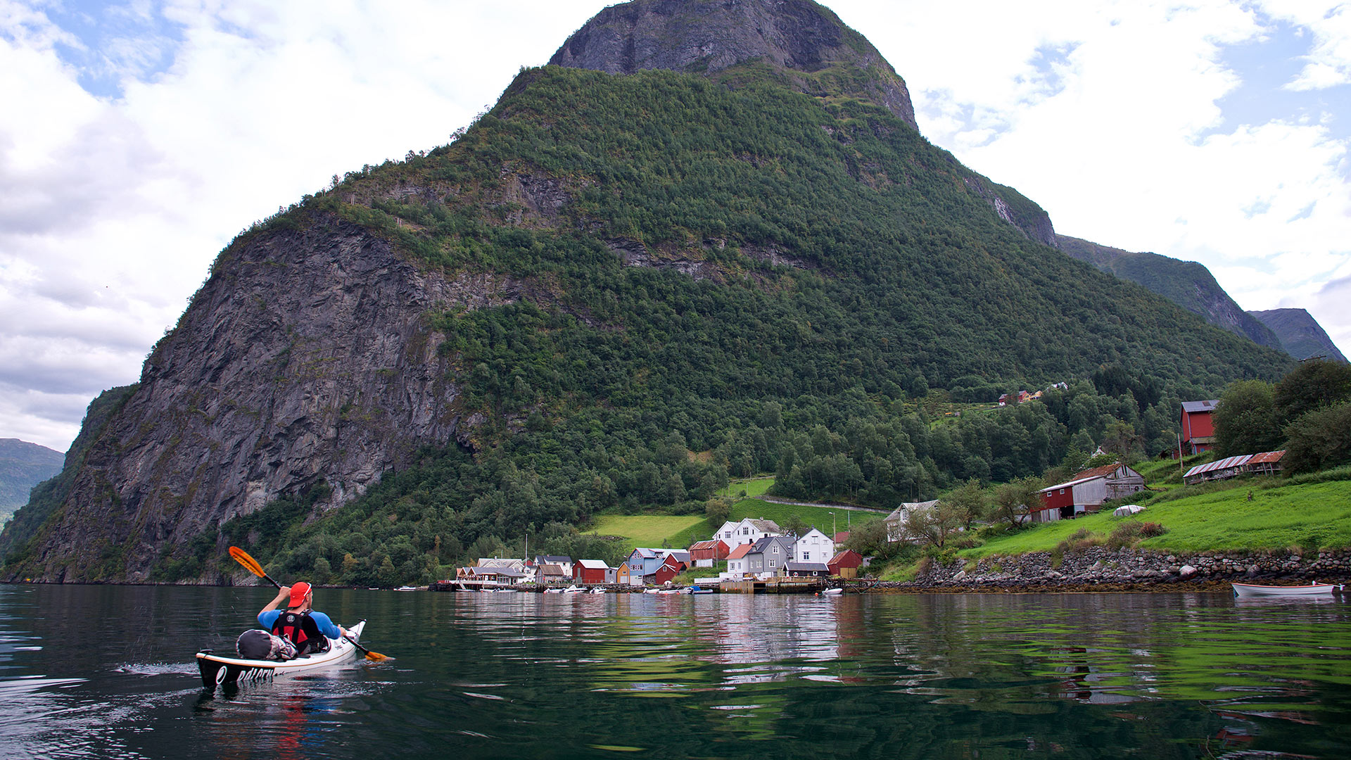 Person paddles on the fjord.