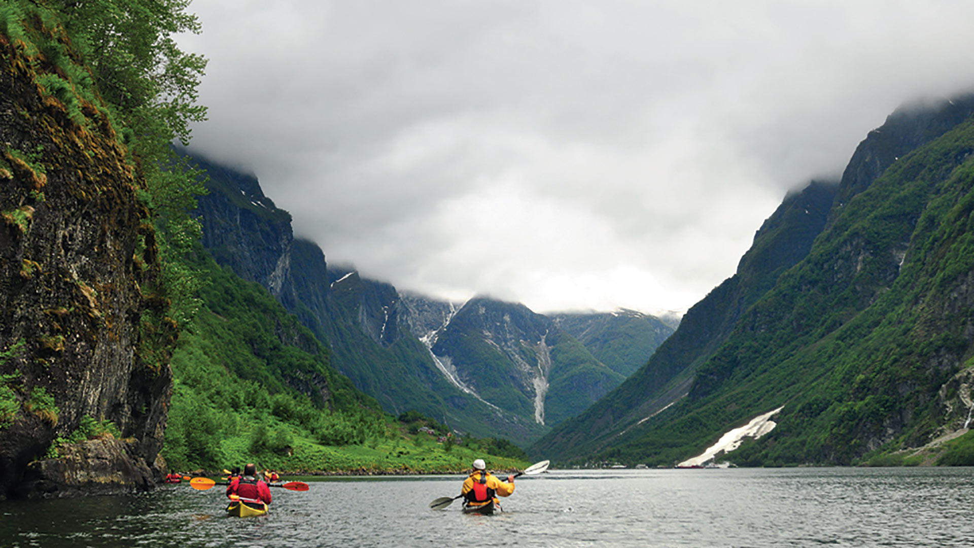 Persons paddle on the fjord.