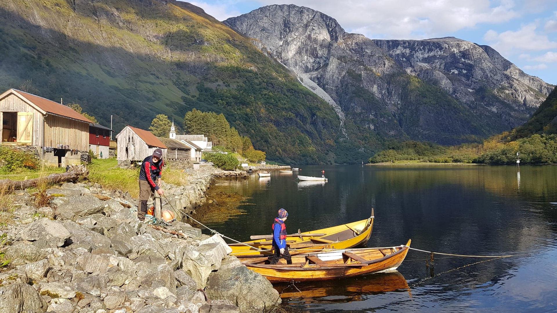 Personer i båt ved fjorden.