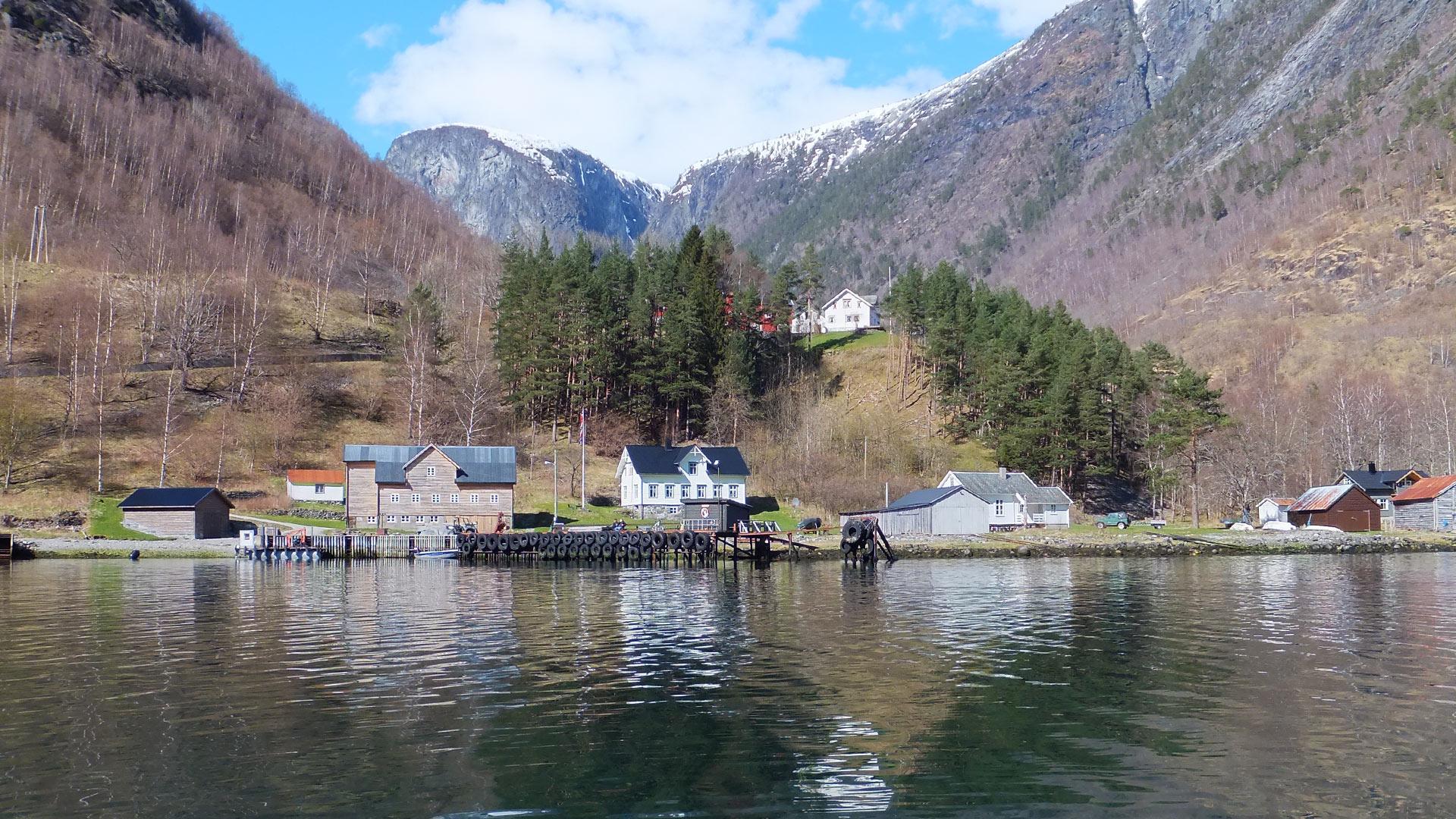 Dyrdal, hus speglar seg mot fjorden.